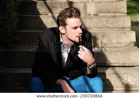 A young attractive man sitting down outside, wearing a black jacket and blue jeans, looking away. Sunny day. - stock photo