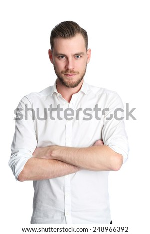 A young attractive man standing against a white background, wearing a white shirt. Feeling great with a smile on his face. - stock photo