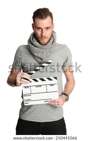A young attractive man wearing a grey shirt and scarf. Standing holding a movie slate against a white background. - stock photo