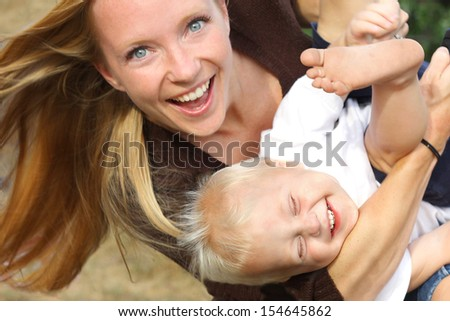 a young, attractive mother is holding her happy, laughing baby boy in her arms, and playing with him outside - stock photo