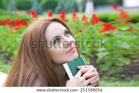 A young attractive woman in her thirties is dreaming about something keeping a read book. - stock photo