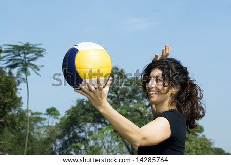 A young, attractive woman is getting ready to spike a volleyball at the park.  Horizontally framed shot. - stock photo