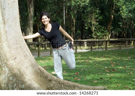 A young, attractive woman is standing next to a tree in the park.  She is smiling and stretching her hamstring.  Horizontally framed photo. - stock photo