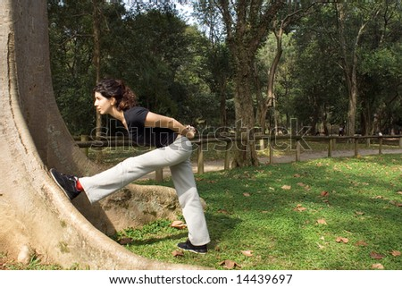 A young, attractive woman is standing next to a tree.  She is looking at the tree, leaning against it and stretching.  Horizontally framed photo. - stock photo