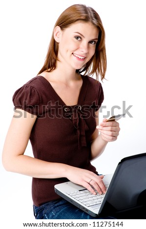 A young attractive woman with laptop and credit card making online purchase - stock photo