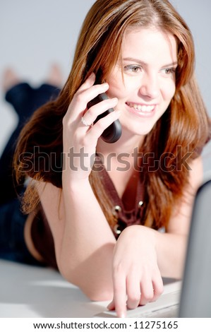 A young attractive woman with laptop and mobile phone (shallow depth of field used) - stock photo