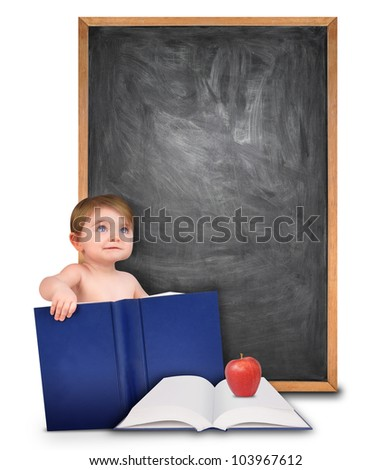 A young baby is holding a book and looking up at a blank black chalk board. There is an open book with an apple for school. Add your text message in the copyspace. - stock photo