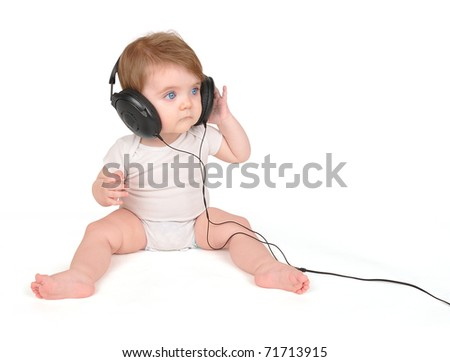 A young baby is sitting on a white isolated background listening to music in black headphones.