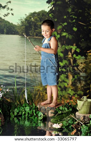 A young, barefoot boy delighted when catching his first fish. - stock photo