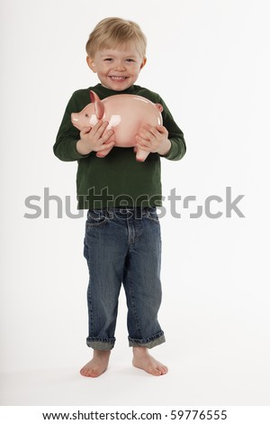 A young, barefoot boy is standing and smiling while holding a piggy bank. Vertical shot. - stock photo