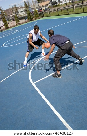 A young basketball player guarding his opponent during a one on one basketball game. - stock photo