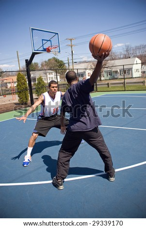 A young basketball player is taunting his opponent with the ball while playing one on one. - stock photo