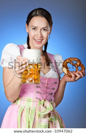 A young Bavarian girl celebrating Oktoberfest with a mass of beer and Brezn - stock photo