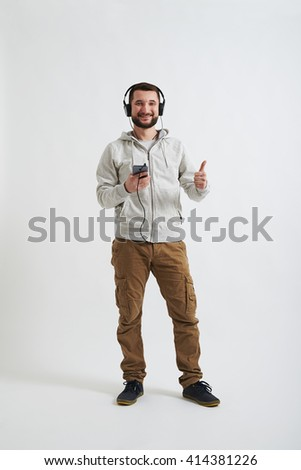 A young bearded man in white hoody and khaki pants is wearing headphones, smiling with his thumb up and holding a phone in his hands - stock photo