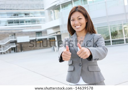 A young, beautiful asian business woman at office building - stock photo