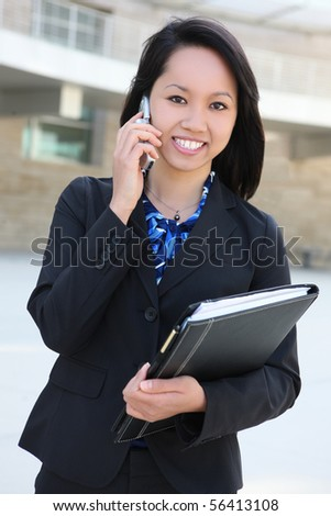 A young, beautiful asian business woman at office on phone - stock photo