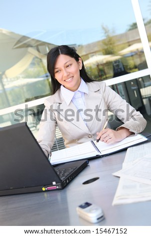 A young, beautiful asian business woman  on laptop computer - stock photo