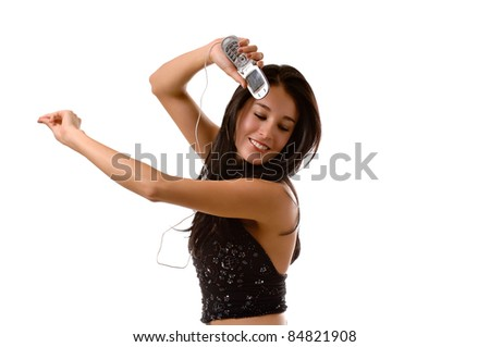 A young beautiful brunette woman, with her eyes closed listening to music on her cell phone.  She is dancing and snapping her fingers. - stock photo