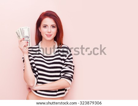 A young beautiful caucasian girl with money on pink background - stock photo