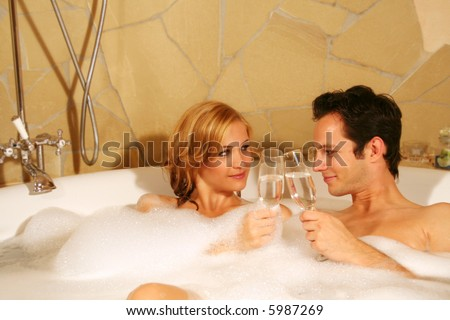 A young beautiful couple is taking a bath with champagne in a glass - stock photo