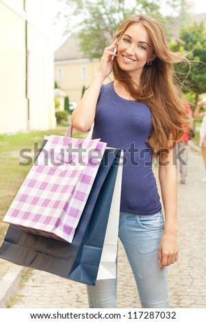 A young beautiful girl calling someone after the purchase - stock photo
