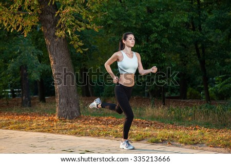 A young beautiful girl is running into the park on cool season at park. 
