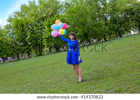 A young beautiful girl playing with balloons outdoors