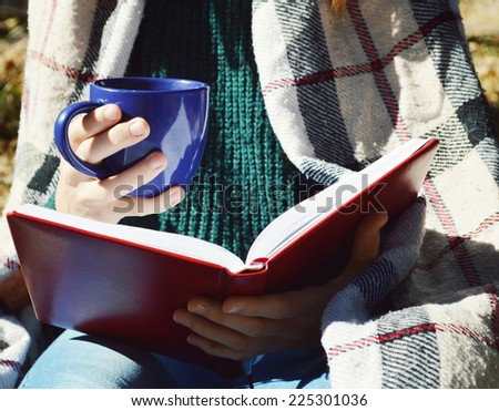 a young,beautiful girl wrapped in a warm plaid blanket drinking hot tea and reading a book in the Park - stock photo