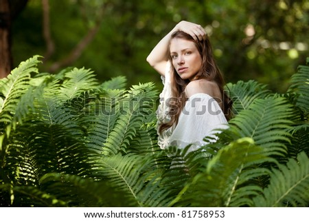 A young, beautiful lady hides and seeks in fern - stock photo