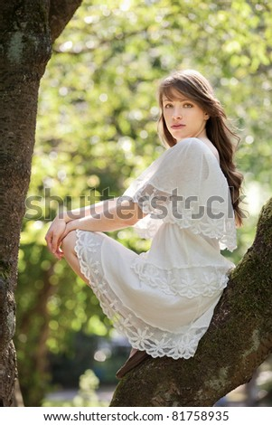 A young beautiful lady is climbing up a tree - stock photo