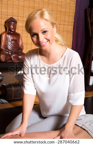 A young beautiful masseuse applying a massage.  - stock photo