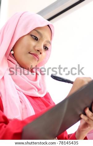 A young beautiful muslim girl writing on report file - stock photo