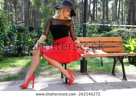 A young beautiful sexy blond woman sitting on a wooden bench in the park with a sweet kitten dressed in sexy red skirt and black blouse with a black hat and a big red sexy shoes - stock photo