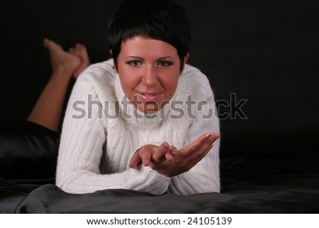 A young beautiful smiling woman wearing white sweater lying on the bed covered with black cloth - stock photo