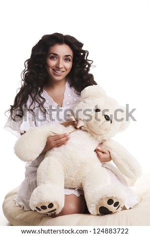 a young beautiful woman hugs a teddy bear - stock photo