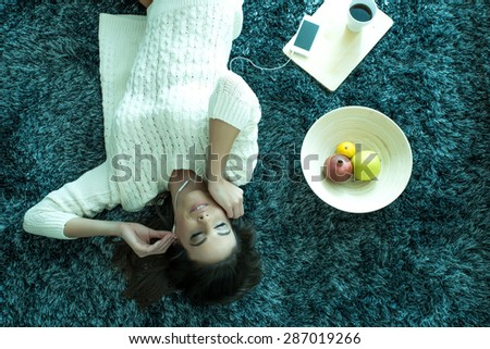 A young beautiful woman in underwear lying on a carpet and listening to music  - stock photo