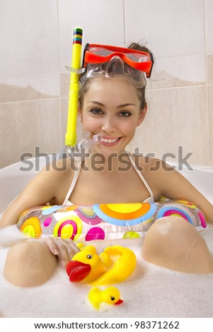 A young beautiful woman is enjoying a bath in mask with snorkel. Playing with his rubber ducky. - stock photo