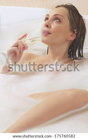 A young beautiful  woman is enjoying a bath with a glasses of champagne - stock photo