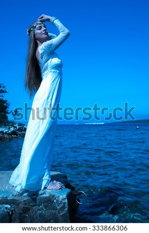 A young beautiful woman standing at the ocean at night. - stock photo