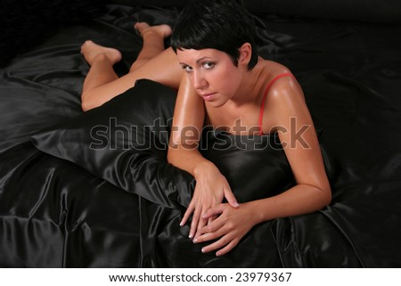 A young beautiful woman wearing underwear lying over black background - stock photo