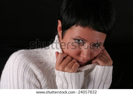 A young beautiful woman wearing white sweater over black background - stock photo