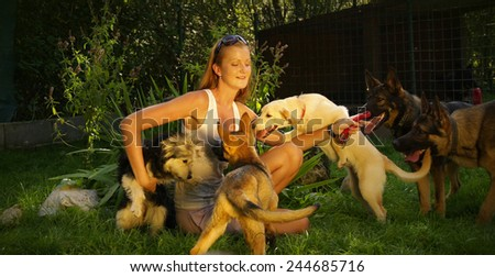 A young beautiful woman with blonde hair is playing with dogs in a backyard with green grass - stock photo