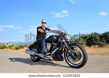 A young biker riding a customized motorcycle on an open road - stock photo