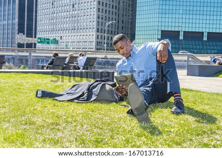 A young black guy is sitting on a lawn in a business district,  reading on a tablet computer. / Study Outside - stock photo
