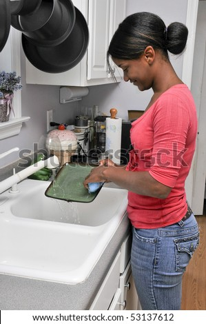 A young black woman doing the dishes - stock photo