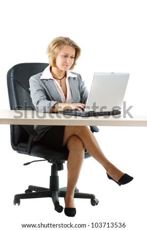 A young blond attractive businesswoman in skirt sitting at her desk and looking attentively at her laptop, full figure with legs is shown - isolated on white - stock photo