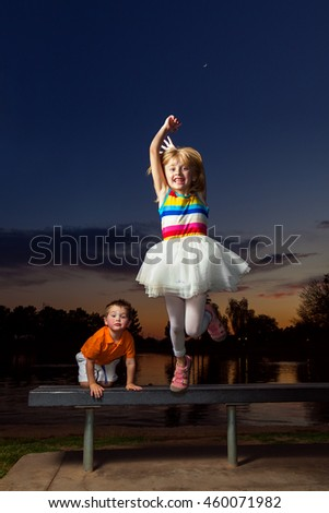 A young, blond girl with a big smile jumps off of a bench a sunset.  Her little brother climbs up behind her with a funny expression.  The girl has her shoes on the wrong feet. - stock photo