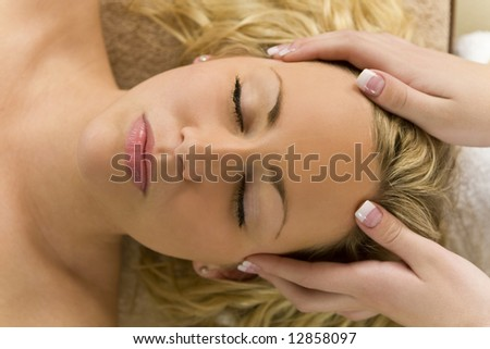 A young blond woman receiving a relaxing head massage from a beauty therapist