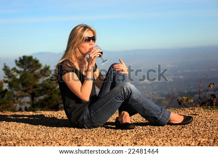 A young blond woman tasting wine outdoors - stock photo