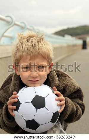 a young blonde boy holding a soccer or football ready to play